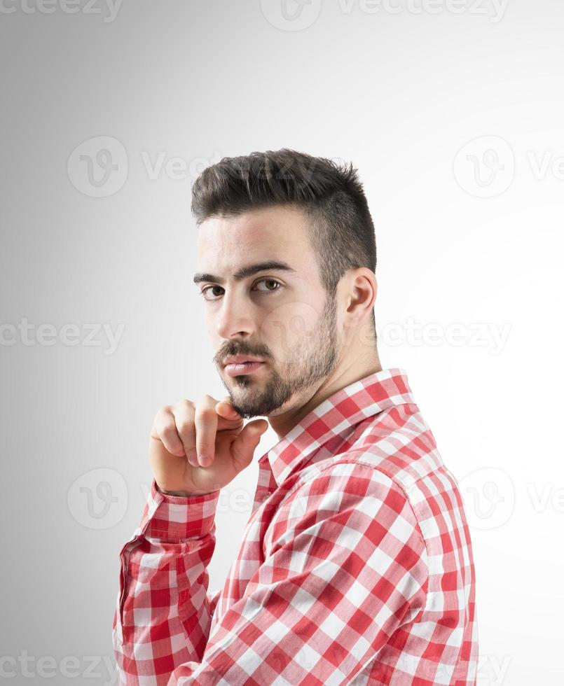 Portrait of confident young bearded man looking at camera photo