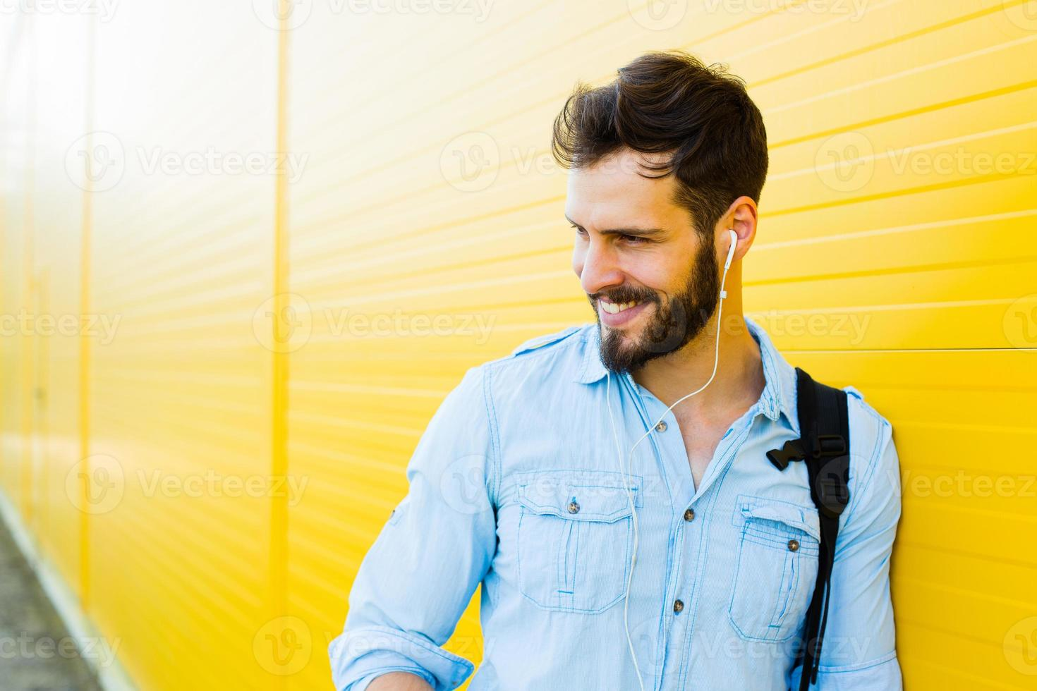 handsome man with backpack on yellow photo