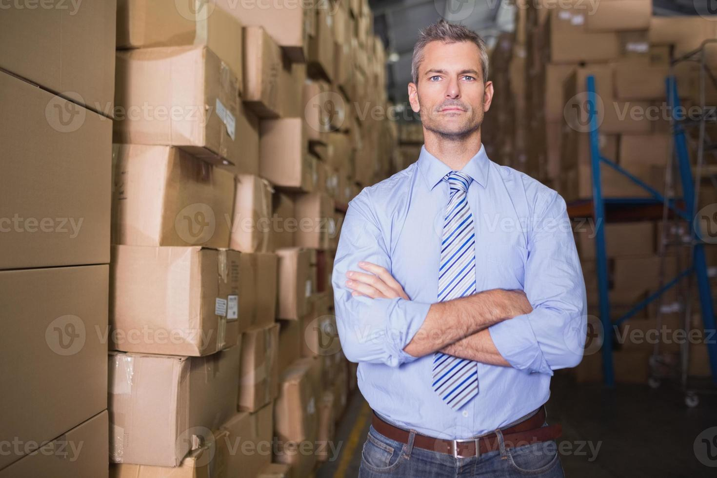 Serious manager with arms crossed in warehouse photo