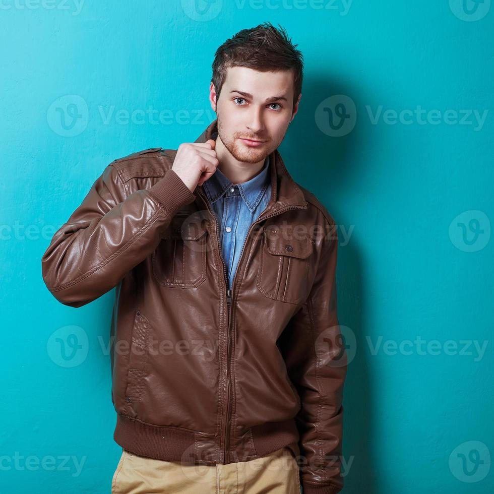 Fashion portrait of the young beautiful man in studio photo