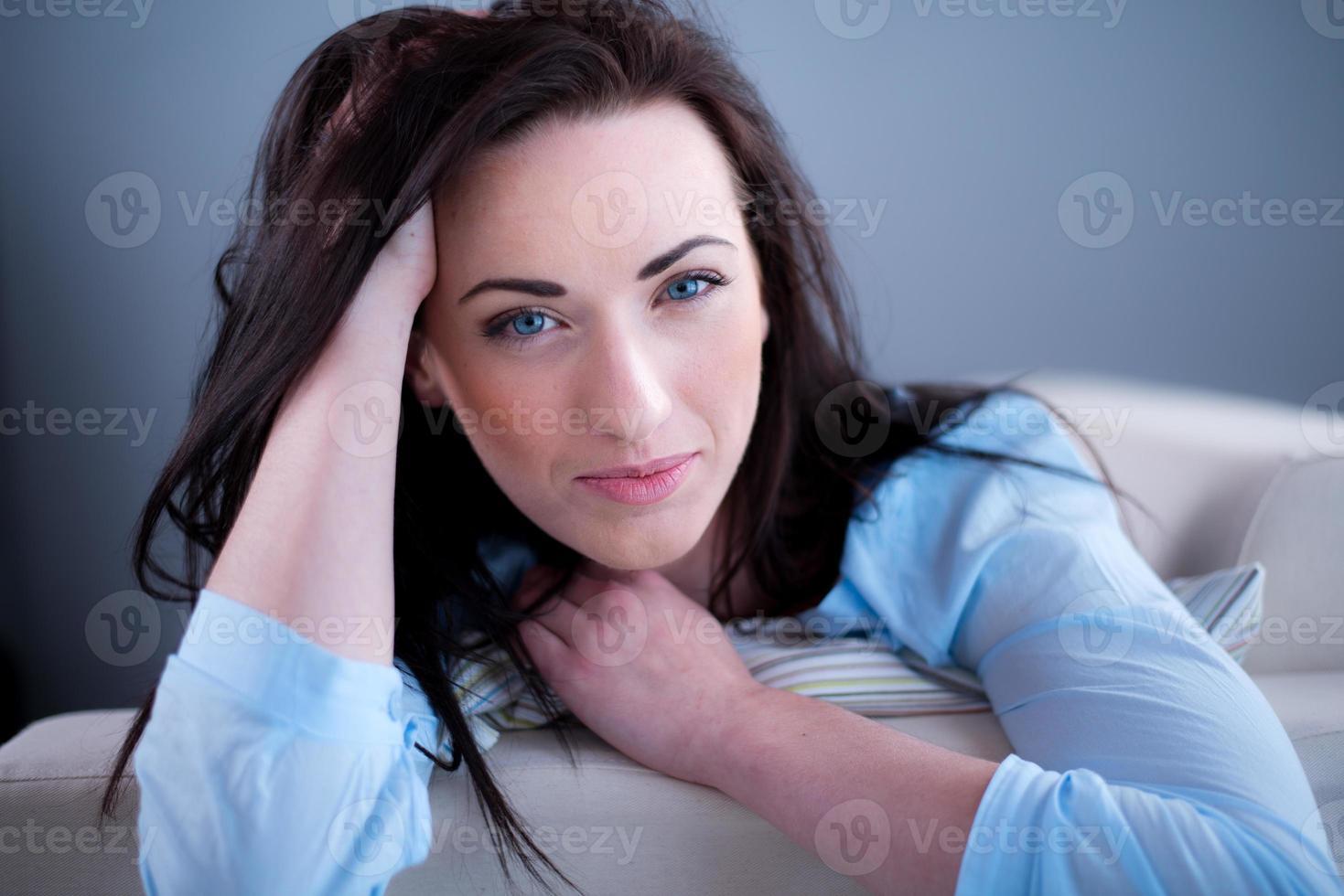 Retrato alegre joven morena acostada en el sofá relajado en casa foto