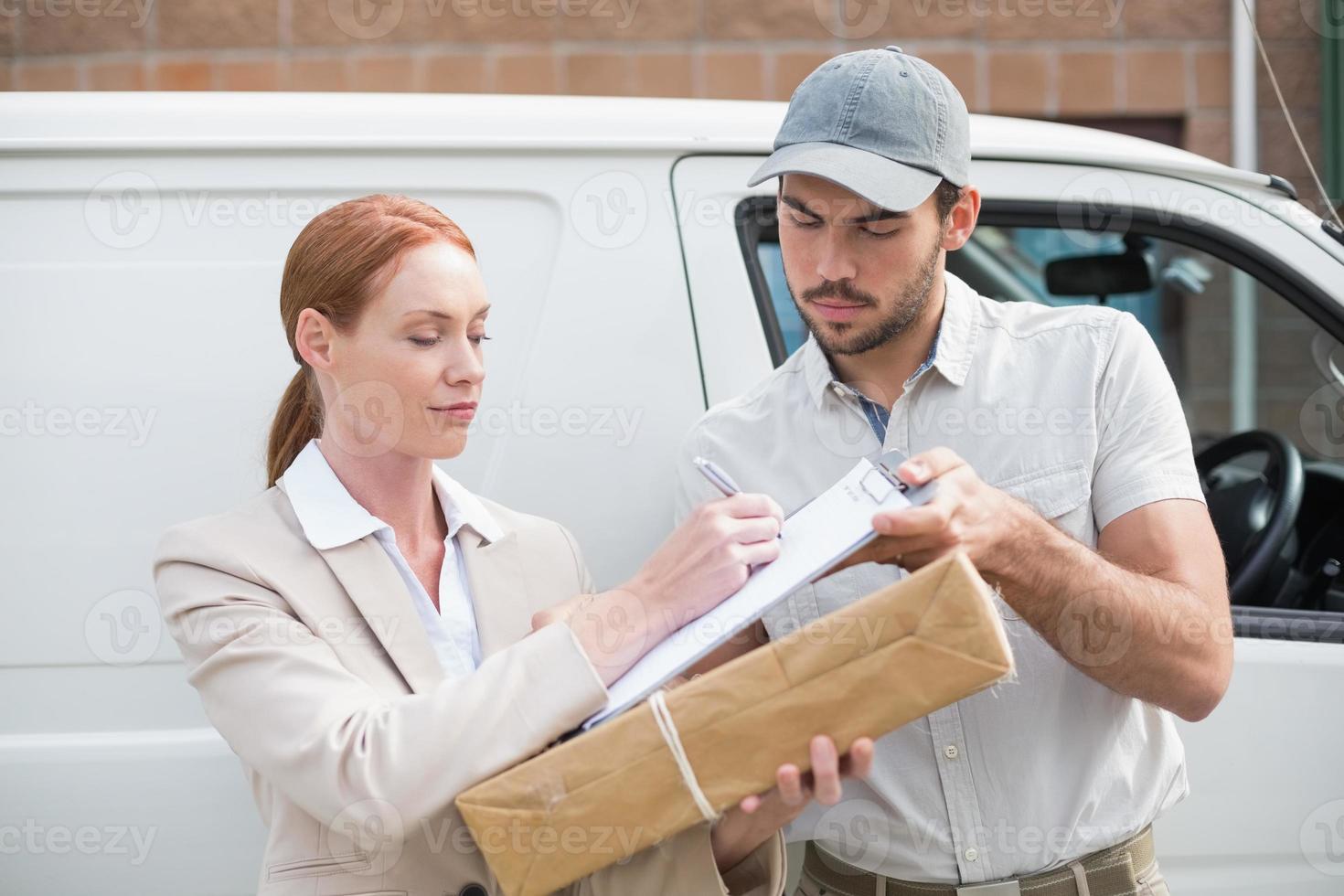 Conductor de entrega que entrega el paquete al cliente fuera de la furgoneta foto