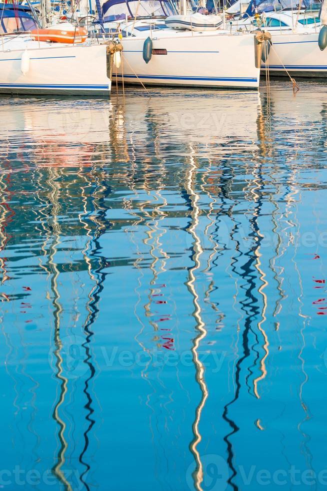 reflejo de los mástiles de los yates en agua de mar foto
