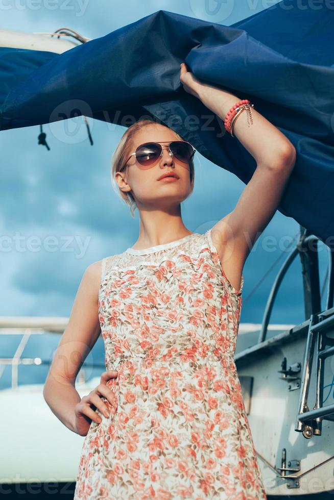 Blonde girl in flower dress and sunglasses holding  boat sails photo