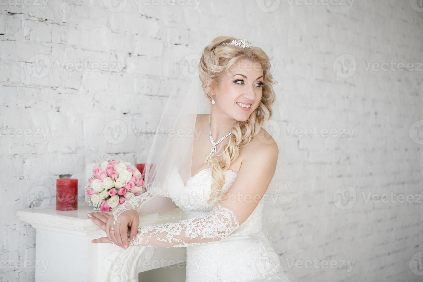 beautiful bride with wedding bouquet standing near fireplace photo
