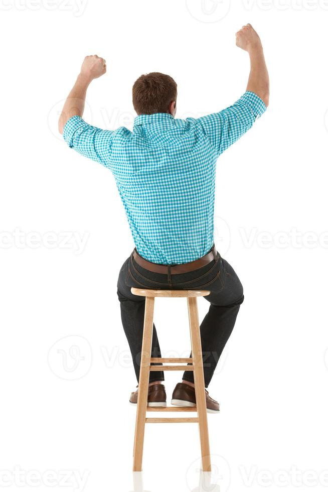 Man sitting on a stool and cheering photo