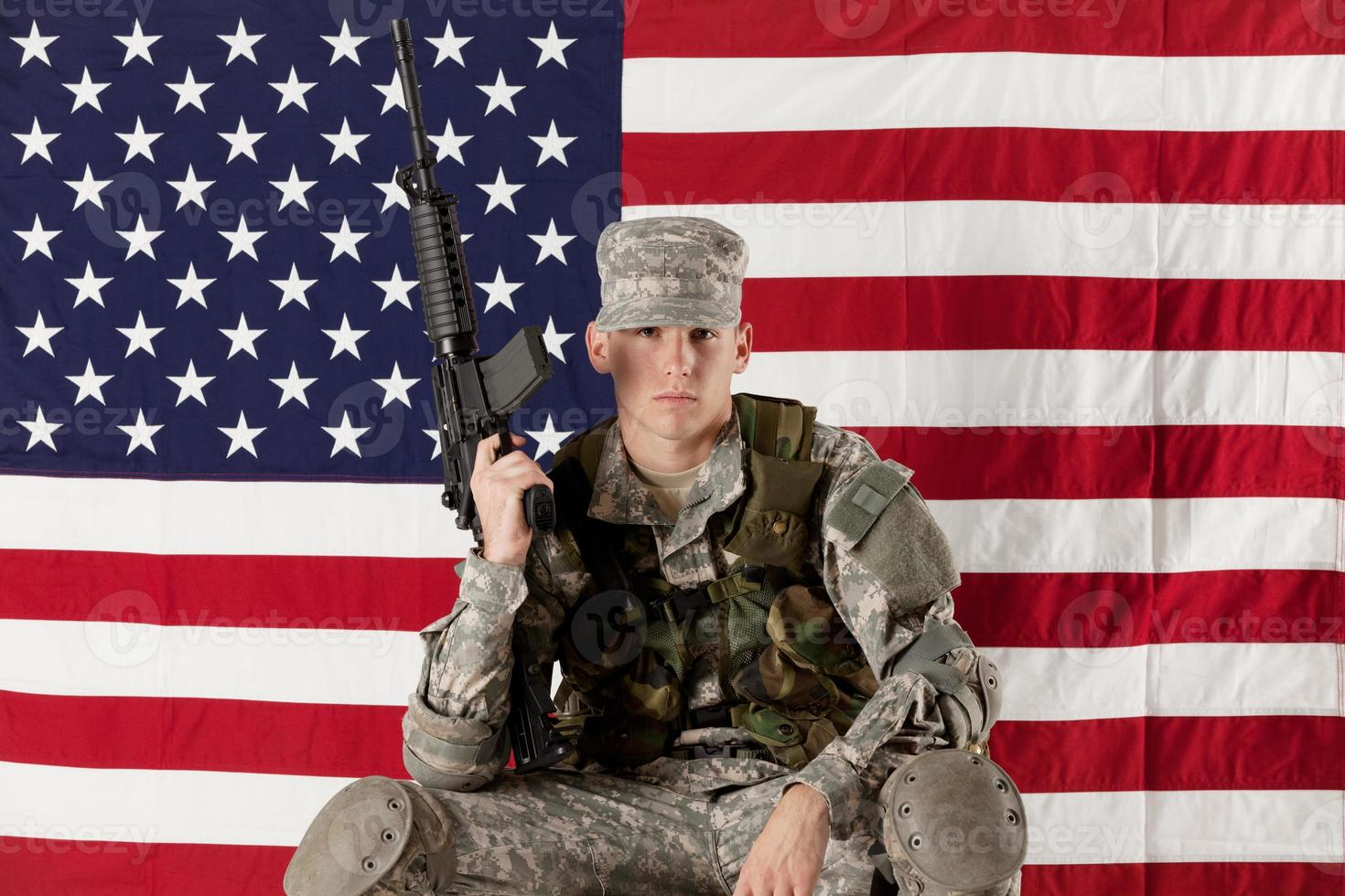 Army man sitting in front of an American flag photo