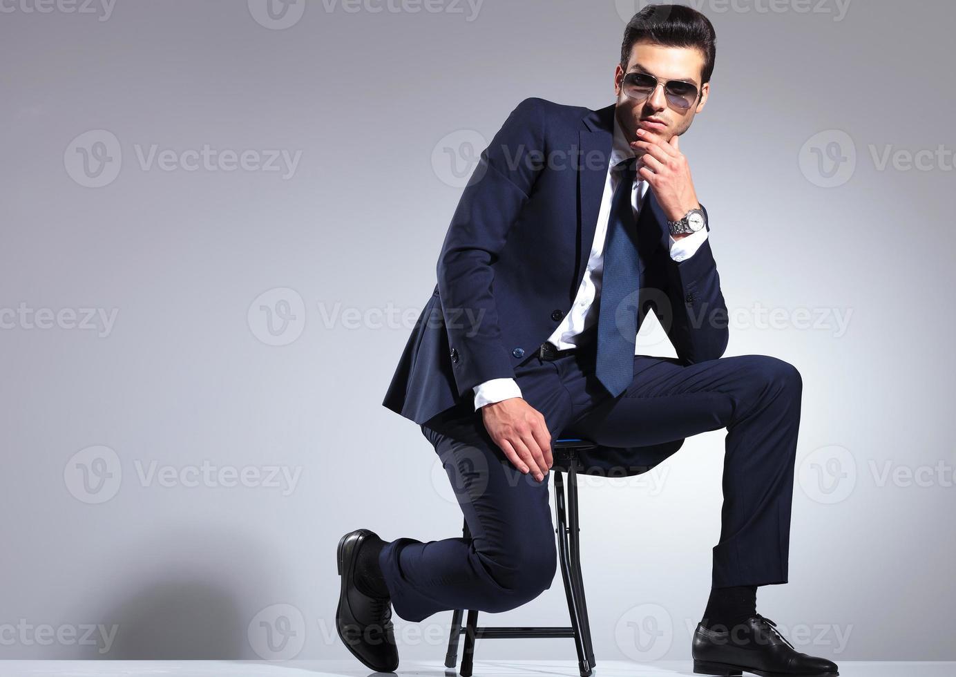 hombre de negocios joven sentado en un taburete foto