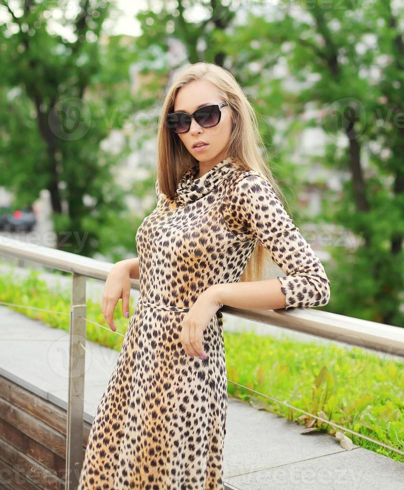 beautiful blonde woman wearing a leopard dress and sunglasses in photo