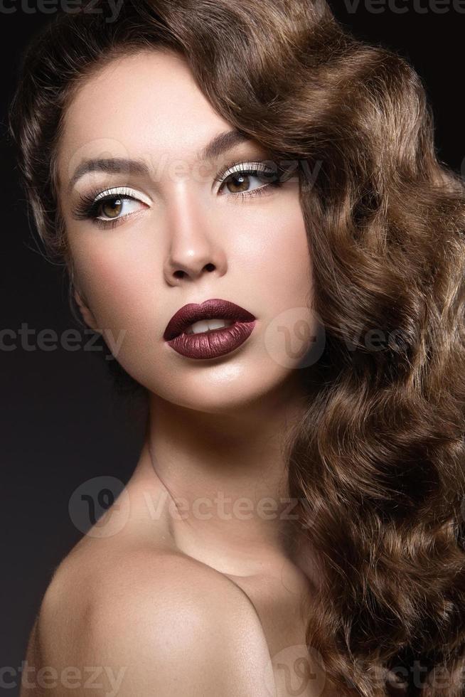 hermosa chica con piel perfecta, labios oscuros y rizos. foto