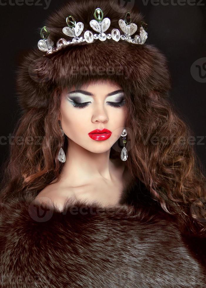 hermosa mujer morena en abrigo de piel de visón. joyería. Moda foto