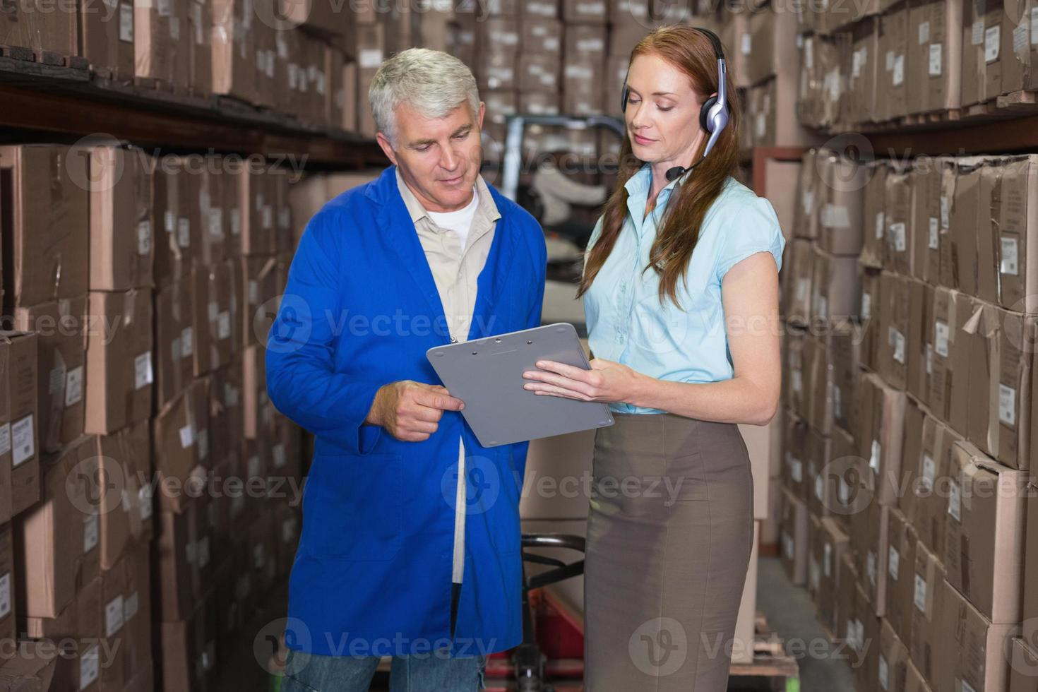 Warehouse manager and foreman looking at clipboard photo