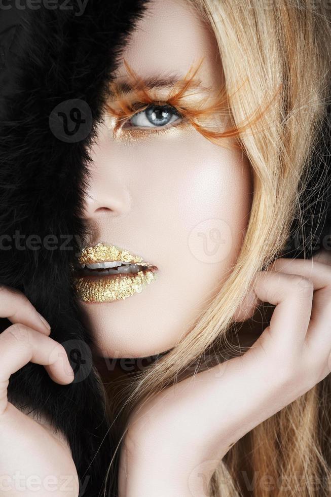 Gold leaf and false eyelashes on a blond woman photo