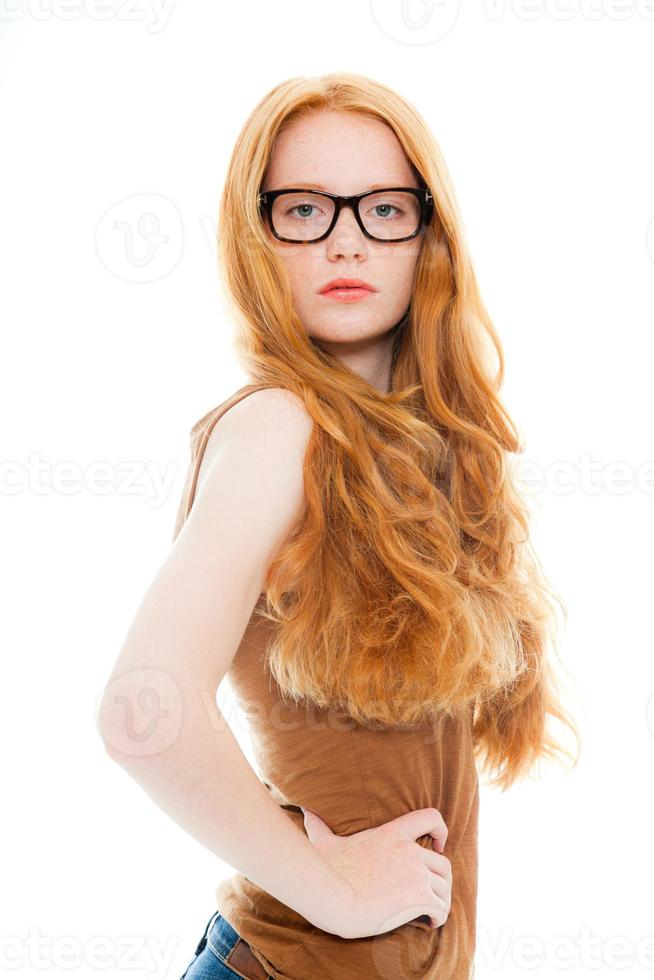 Pretty girl with long red hair wearing retro glasses. photo