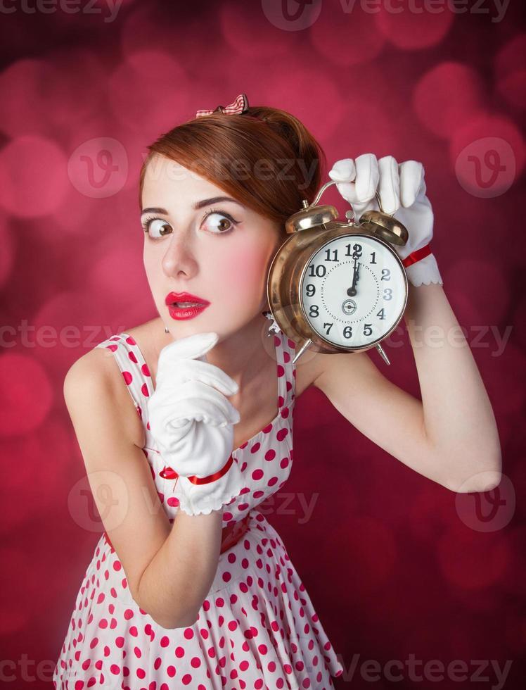 Beautiful redhead women with clock. photo