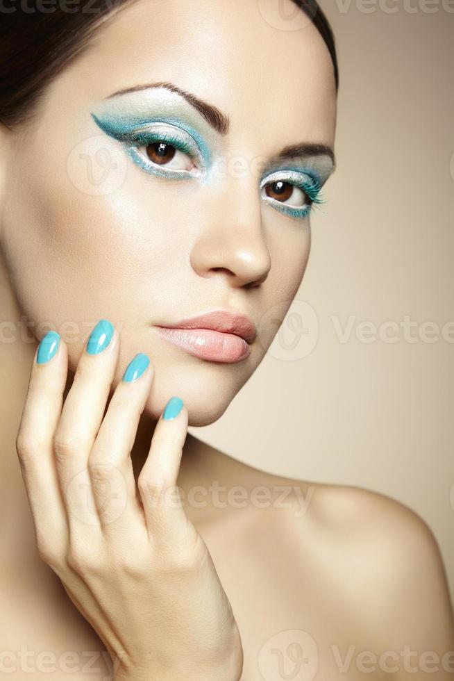 Beautiful young woman with bright make-up and manicure photo