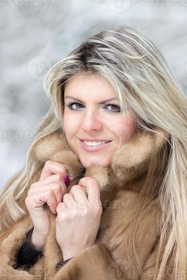 mujer joven en abrigo de piel en invierno al aire libre. foto