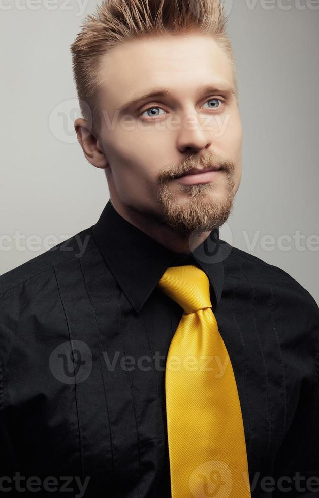 Elegant young handsome man in black shirt & yellow tie. photo