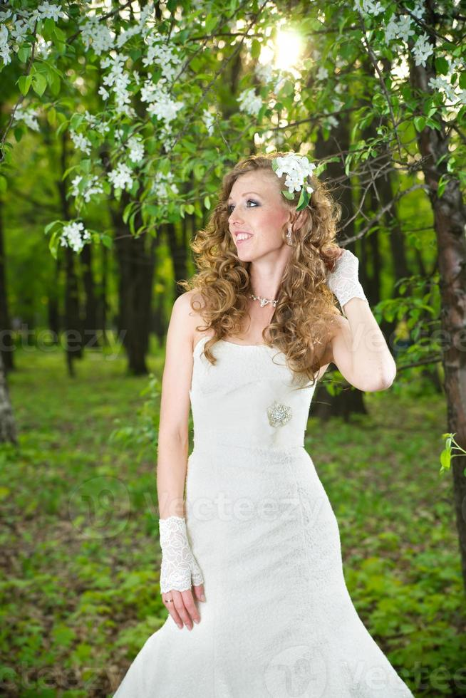 Beautiful bride in white dress on blooming gardens photo