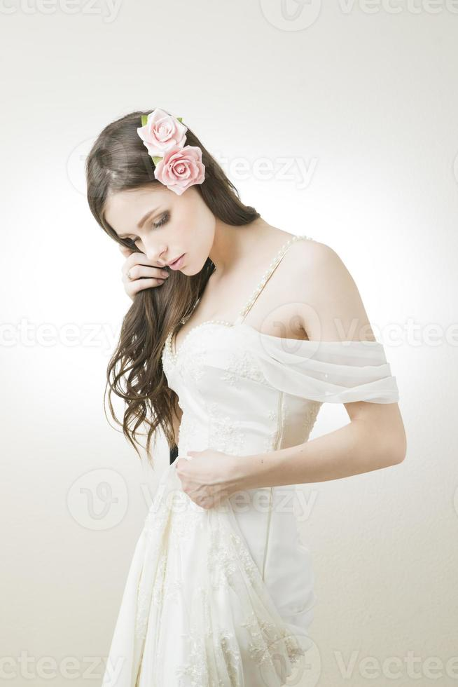 Studio portrait of young beautiful bride in a white dress photo