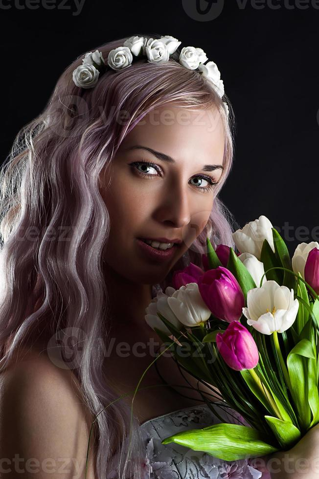 fashion woman face with a bouquet of tulips photo