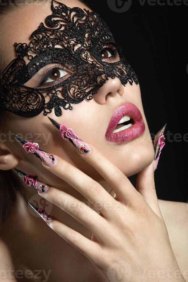 hermosa chica en una máscara con uñas largas. foto