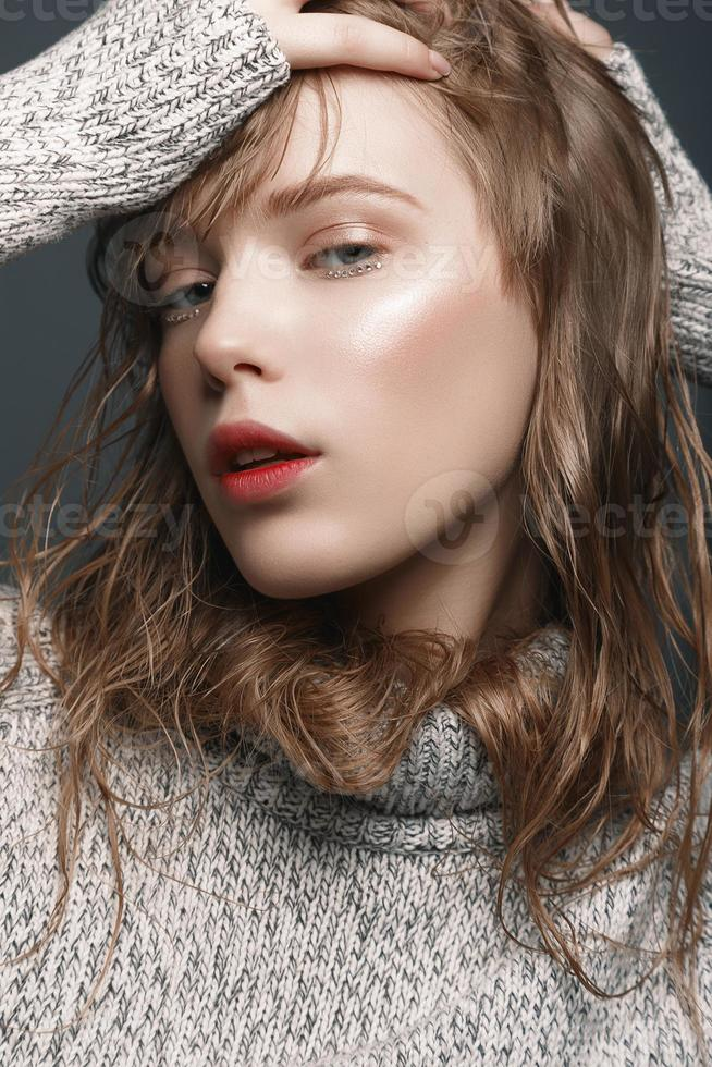 Portrait of a young girl in sweater studio photo