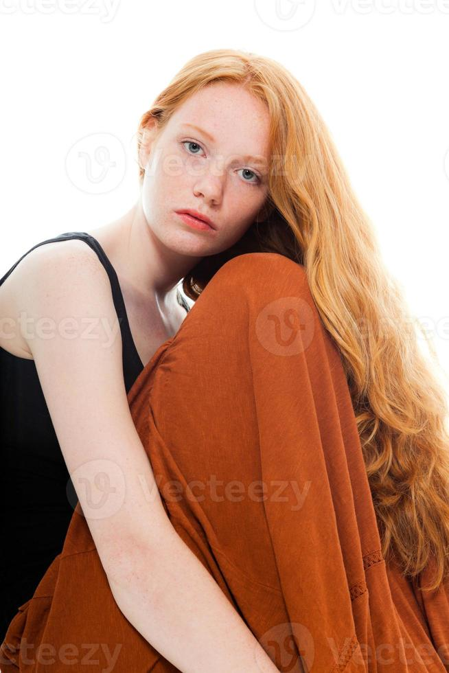 Pretty girl with long red hair wearing brown dress. photo