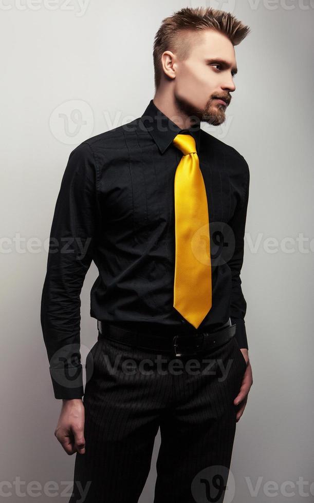 elegante joven apuesto con camisa negra y corbata amarilla. foto