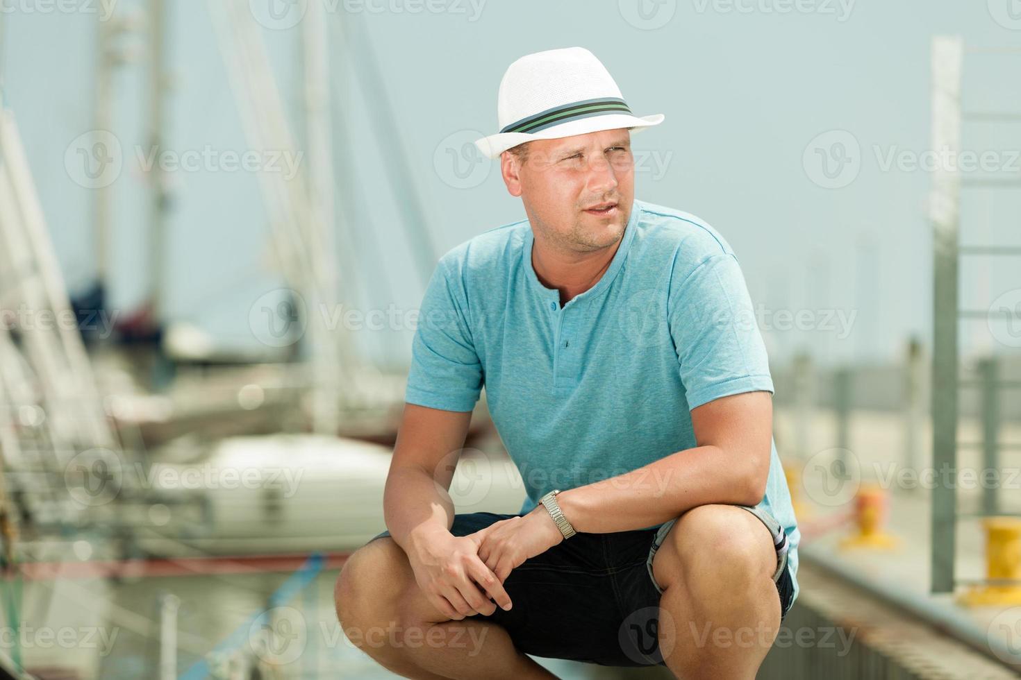 mode portret van knappe man op pier tegen jachten foto