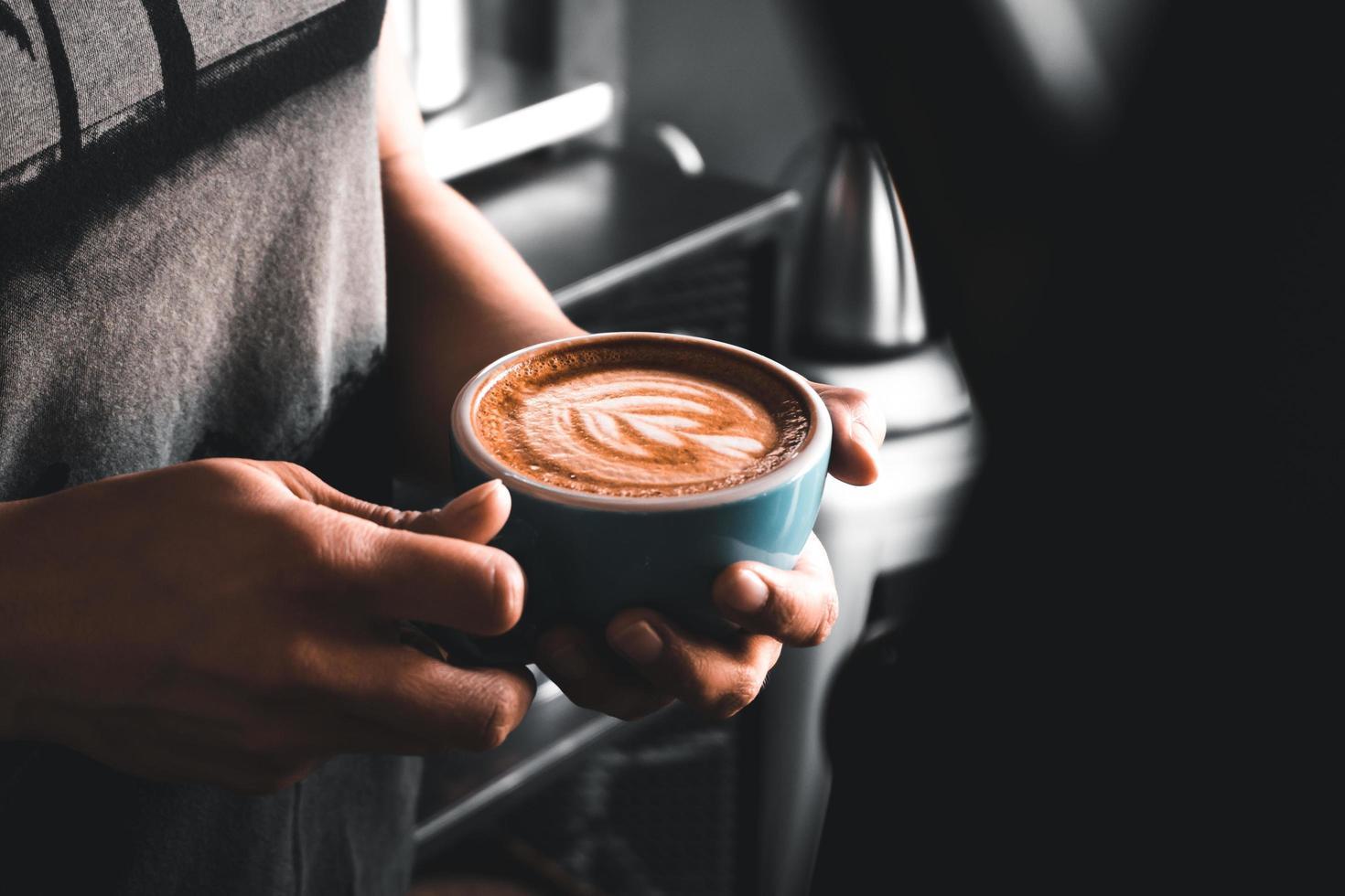 persona sosteniendo una taza de cafe foto