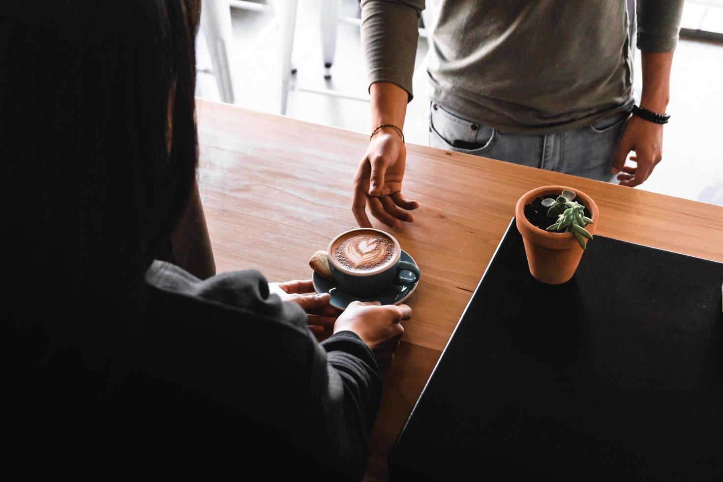 persoon achter balie die koffie aan klant overhandigt foto