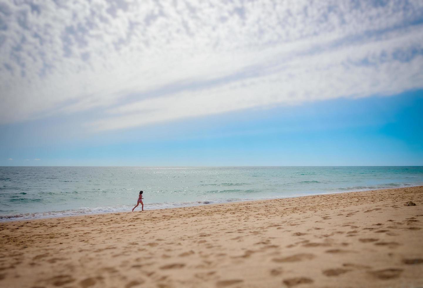 solo persoon loopt op strand foto
