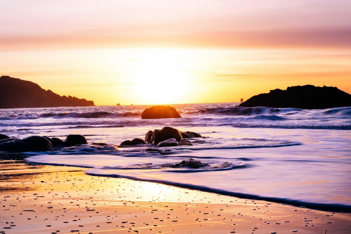 puesta de sol sobre el horizonte en una playa foto
