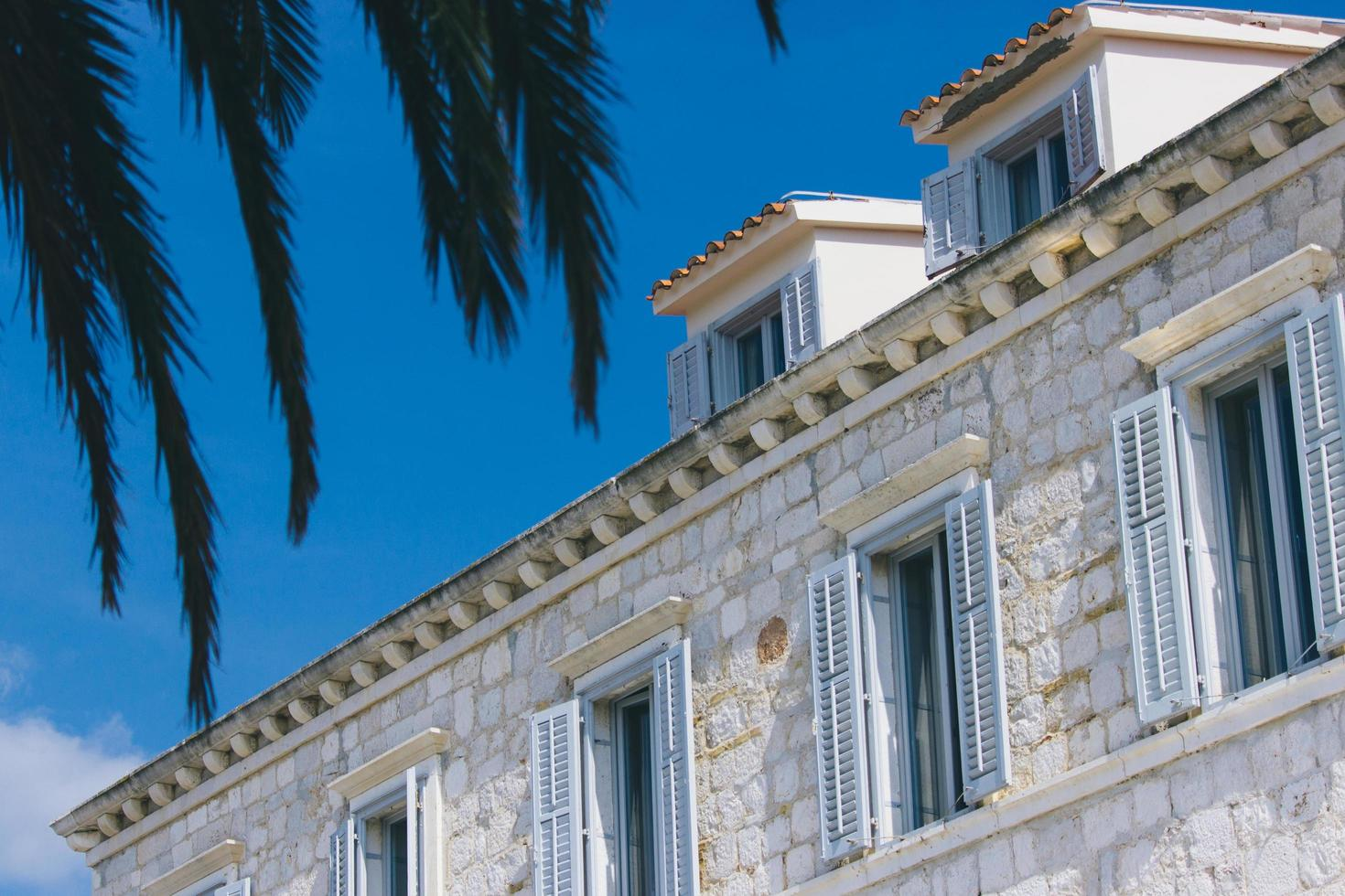 Casa de piedra blanca mostrando persianas de ventana foto