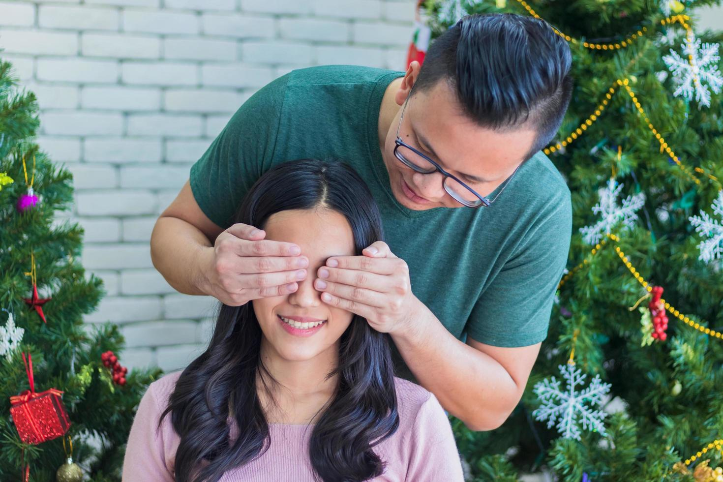 Man surprising woman with Christmas trees in background photo