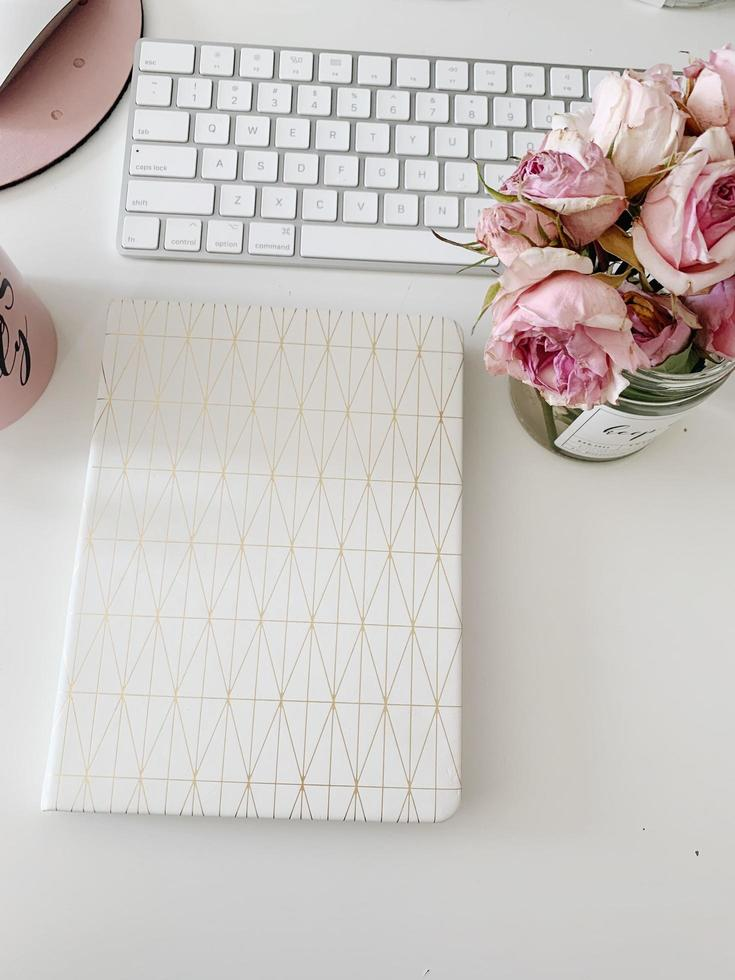 White covered book, keyboard and flowers photo