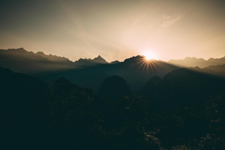 sagoma di montagne durante il tramonto foto