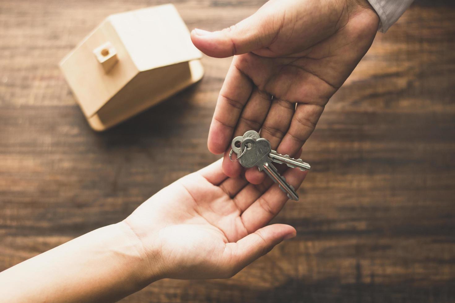 Agente inmobiliario dando llaves al cliente. foto