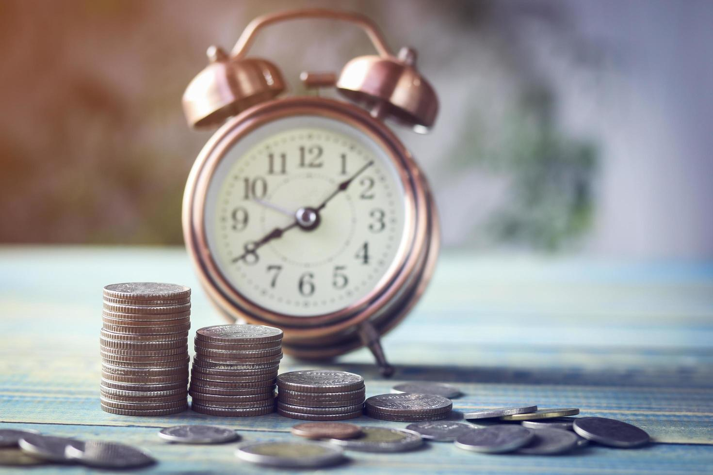 pila de monedas con reloj despertador rojo foto