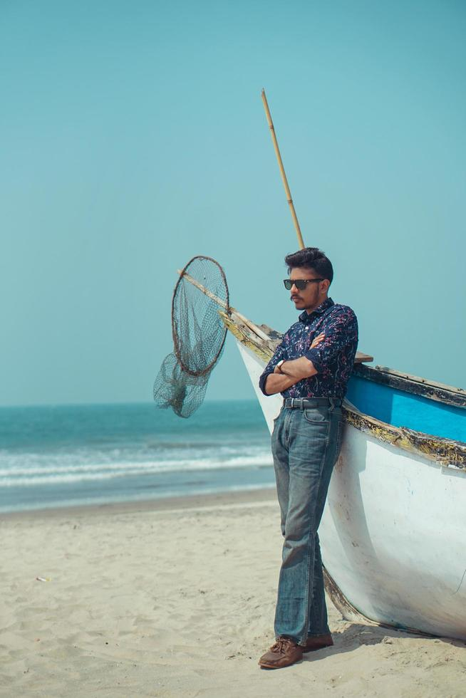 Young man standing with a boat near beach photo