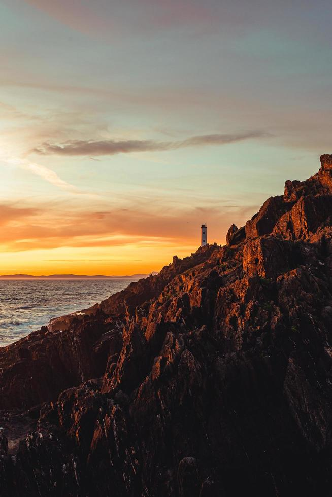 A dramatic view of a white lighthouse from the rocks of the coast photo