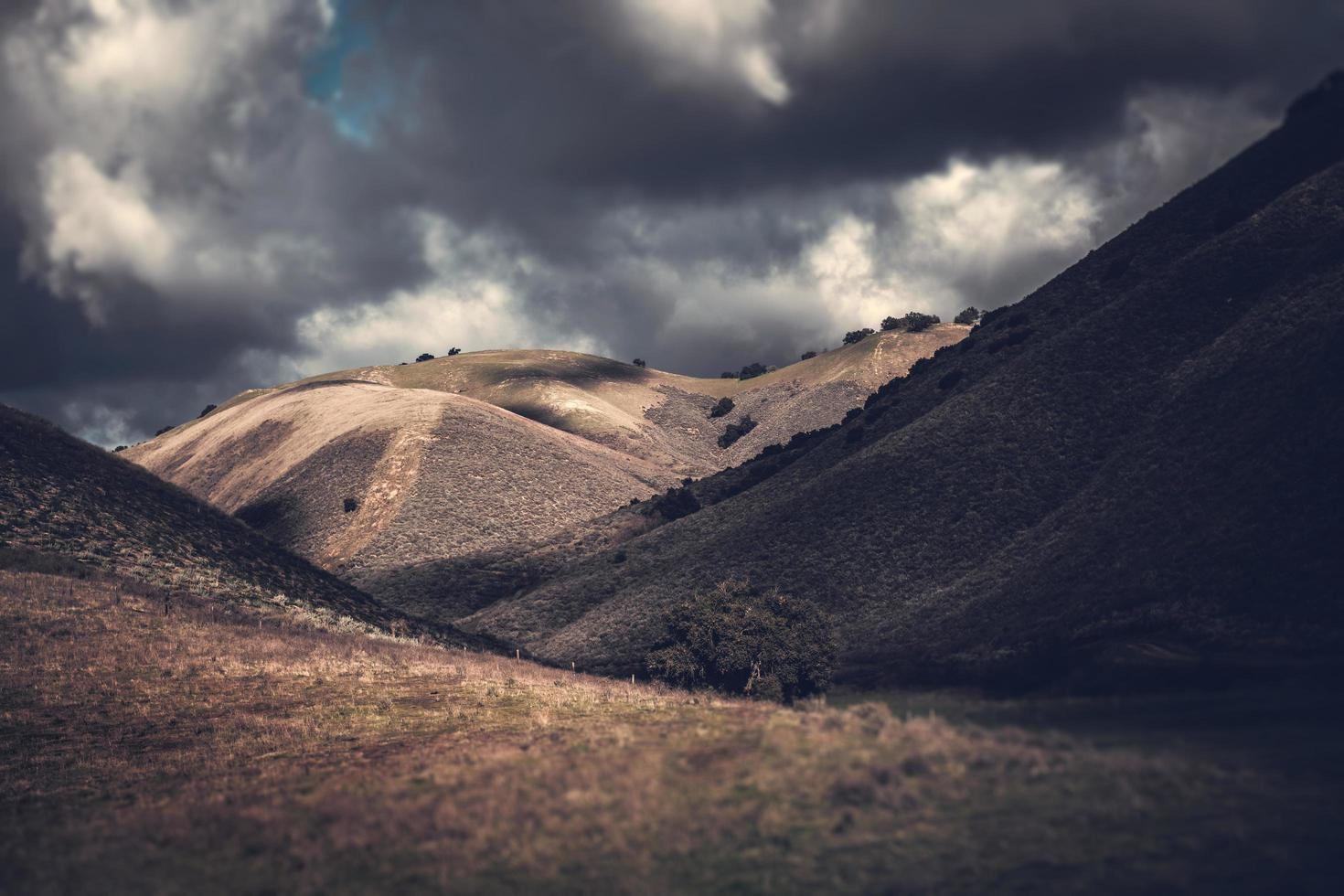 Tilt shift of mountain under dramatic clouds photo
