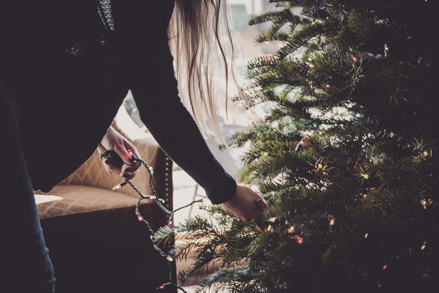 mujer decorando arbol de navidad foto