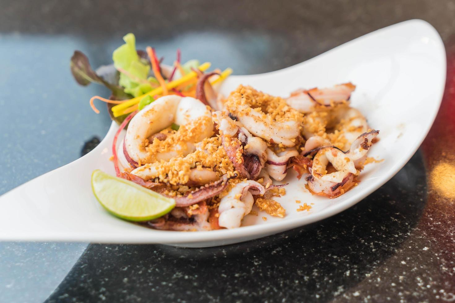 Fried squid with garlic on a plate photo