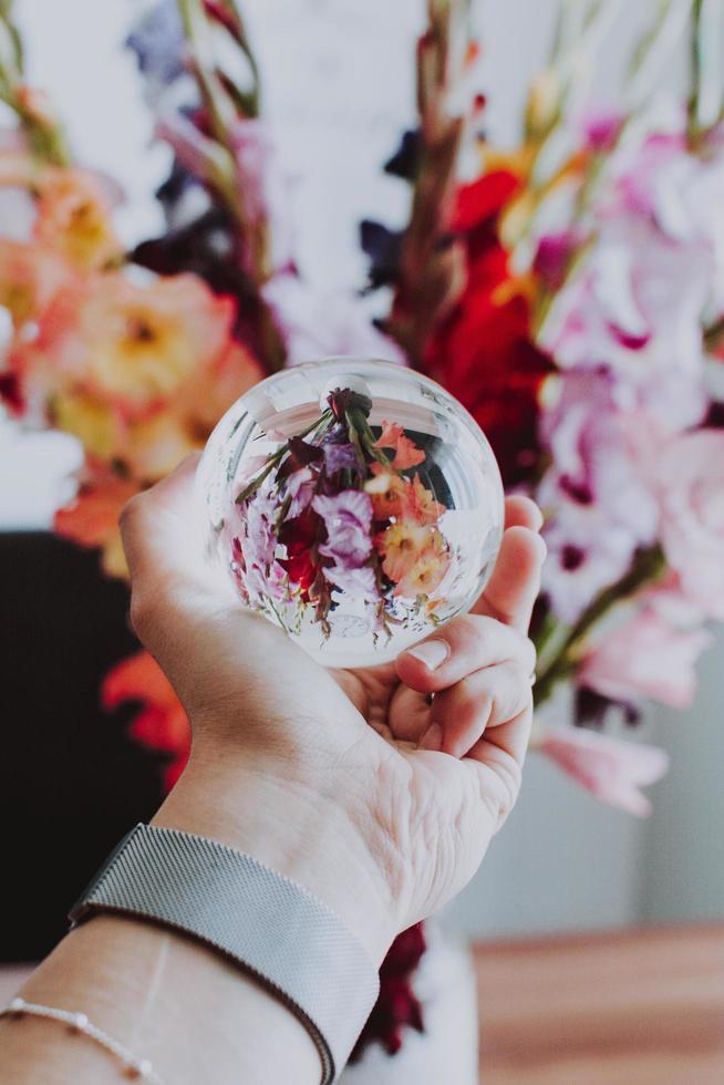 persona sosteniendo un lensball delante de flores foto