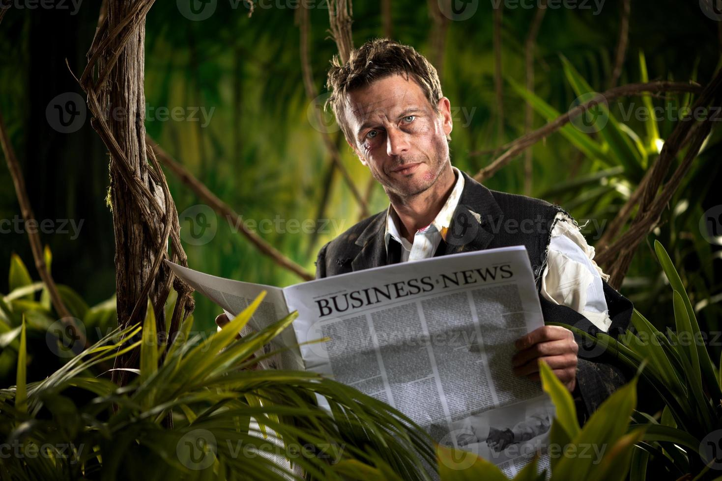 Businessman reading financial news in the jungle photo