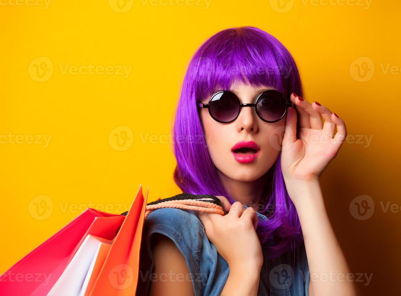 Women with violet hair with shopping bags. photo