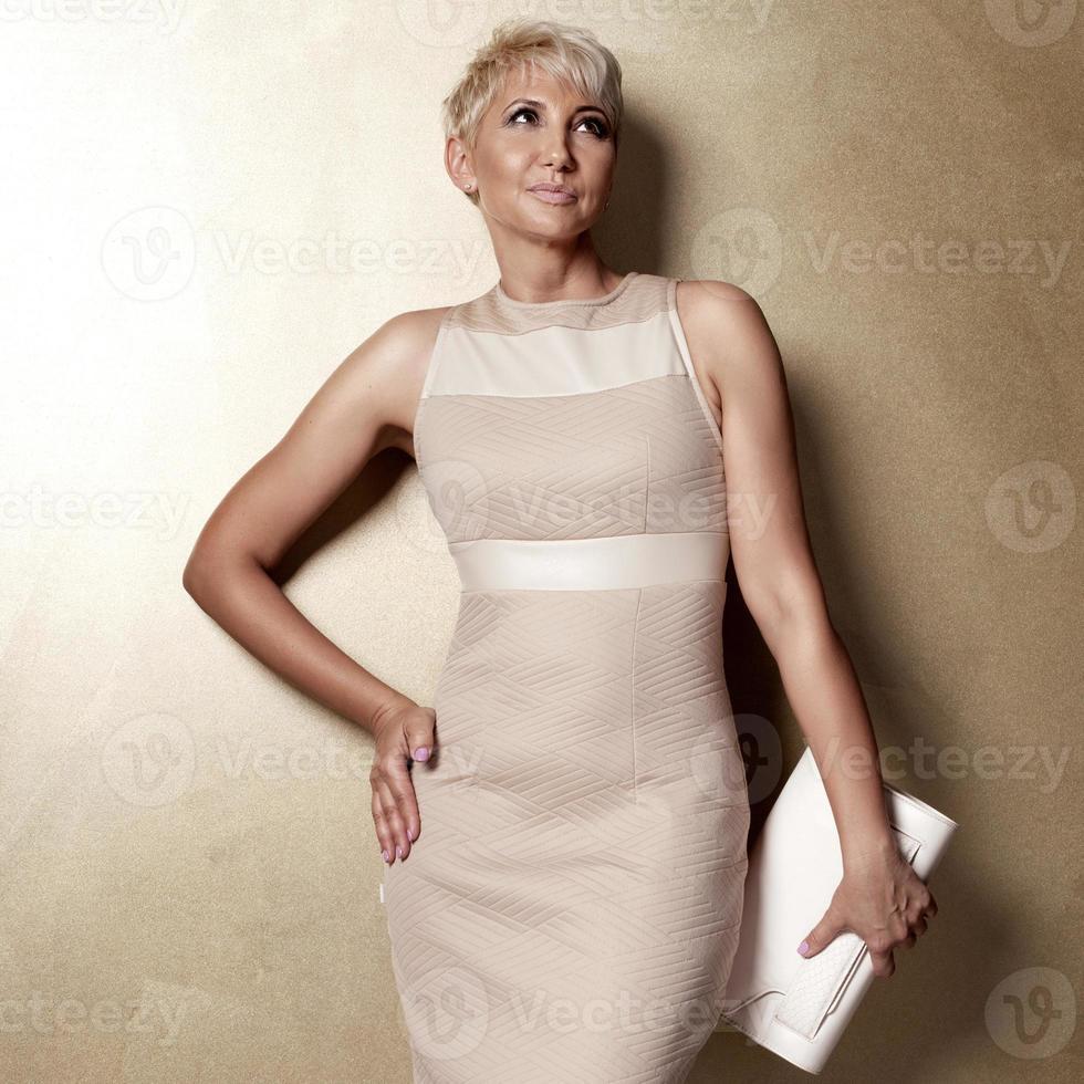 elegant blonde woman in fashionable dress. photo
