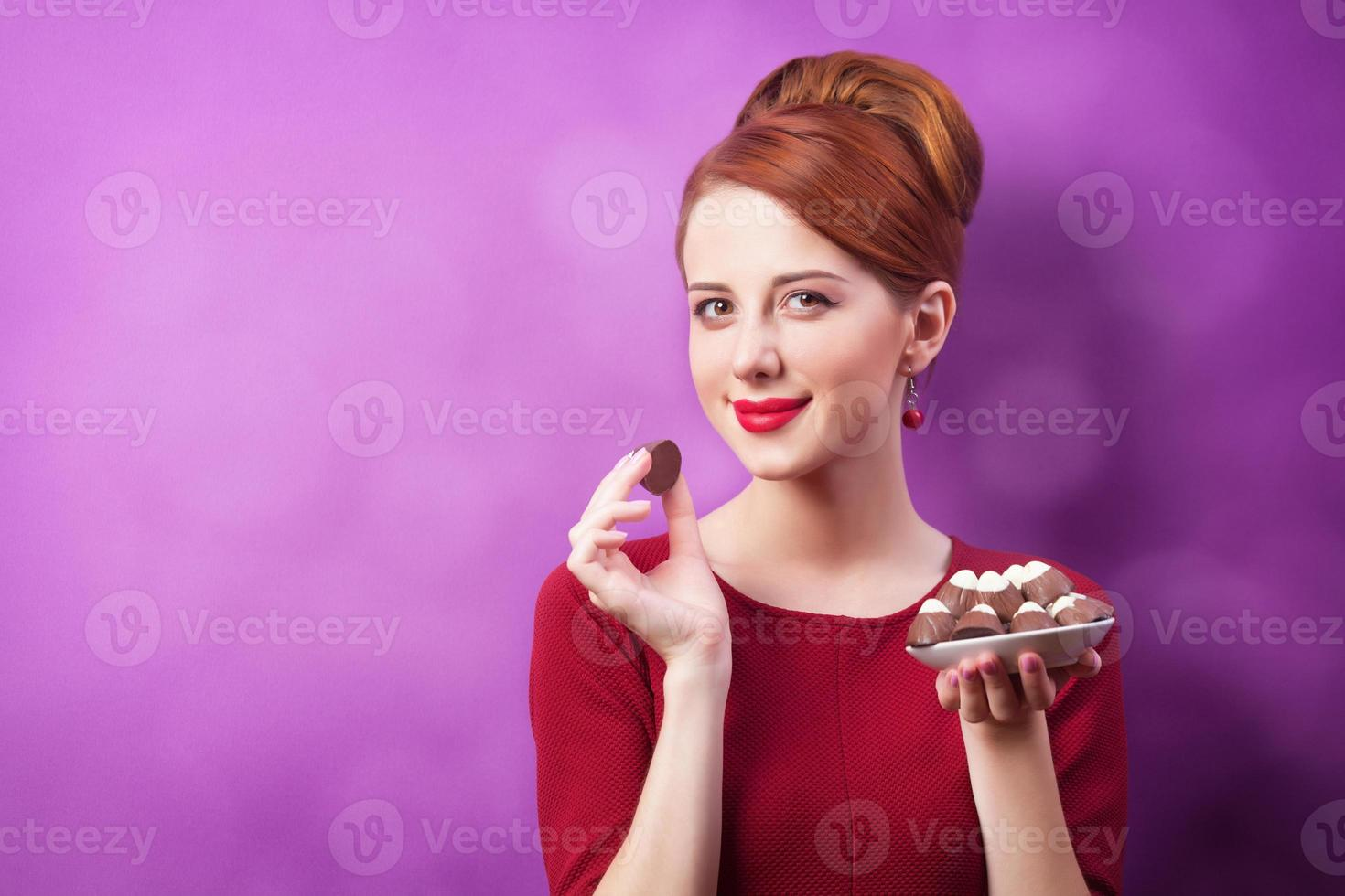 Redhead women with candy on violet background. photo